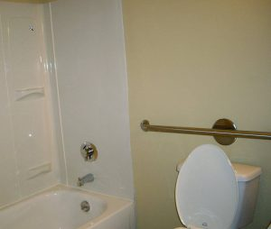 bathroom with grab bar handle for safety near toilet